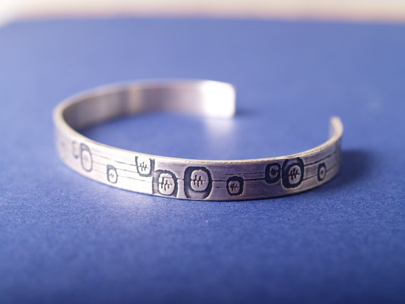 sterling etched cuff featuring an abstract floral design shown on a blue field