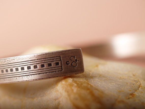 narrow, flat, sterling etched cuff with the design of a skyscraper running from one side to the other on its side. image of artist mark at the end of cuff