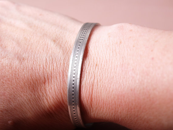 narrow, flat, sterling etched cuff with the design of a skyscraper running from one side to the other on its side. image of cuff worn on a wrist
