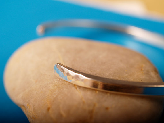 narrow sterling cuff with flared hammered center and ends with shiny smooth space between center and ends shown on a stone