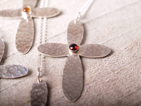 sterling hammered cross with rounded ends with a round garnet cabochon set in the middle shown on grey wood background
