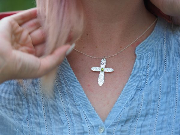 sterling hammered cross with rounded ends featuring peridot photo on model