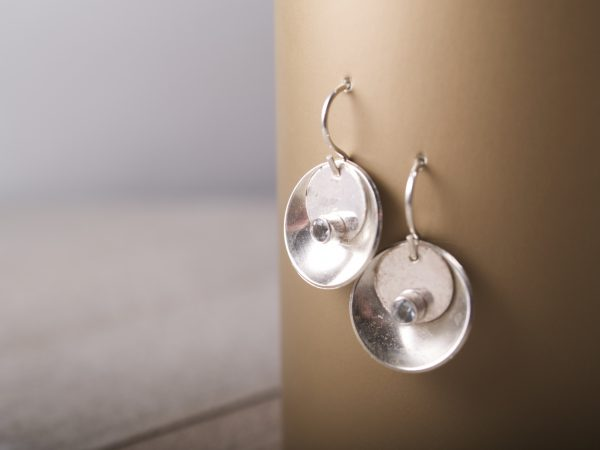 silver concave earrings with a smaller silver desk that sits inside the concave disk with a round faceted aquamarine set at the bottom of the flat disk shot hanging on bronze background