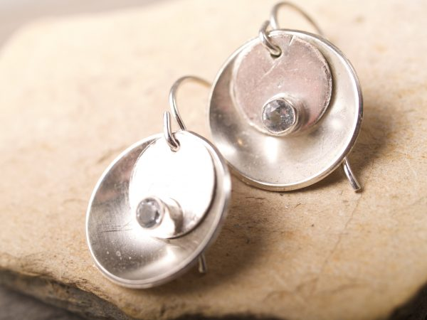 silver concave earrings with a smaller silver desk that sits inside the concave disk with a round faceted aquamarine set at the bottom of the flat disk shot on sandstone