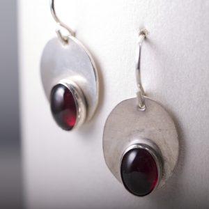 Sleek sterling oval earrings with garnet cabochons