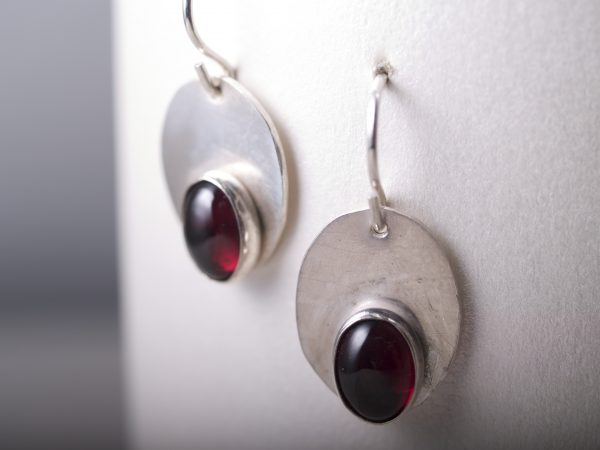 smooth shiny sterling silver oval earrings with red oval garnet stones closeup shot hanging on white background