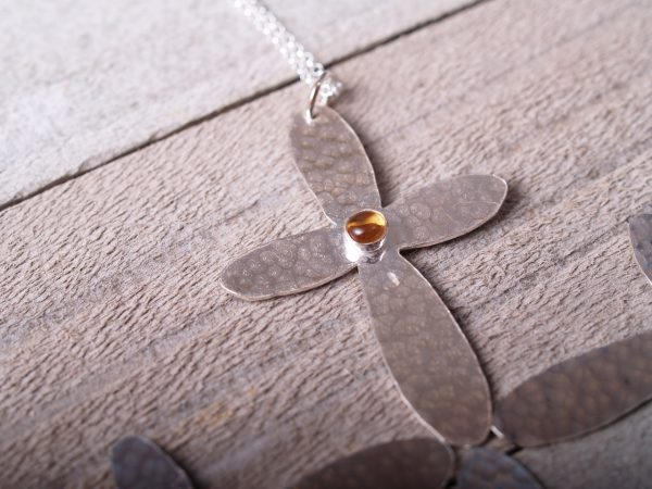 sterling hammered cross with rounded ends with a round citrine cabochon set in the middle shown on wood background
