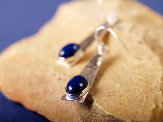 lapis cabochons set in hammered sterling cabochons with french hook earrings shot on sandstone and blue