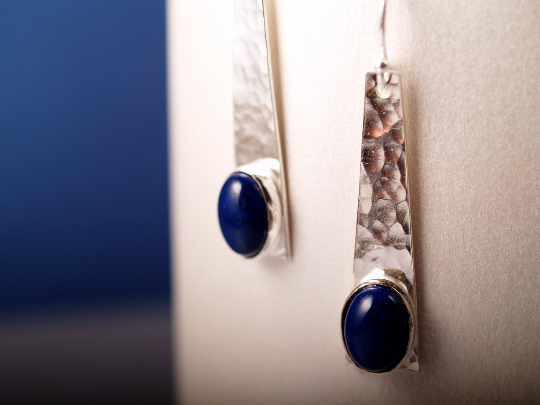 lapis cabochons set in hammered sterling cabochons with french hook earrings hanging on white and blue