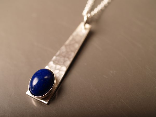 sterling trapezoid pendant with hammered finish and oval lapis cabochon set toward the bottom on a sterling chain on smoke grey background
