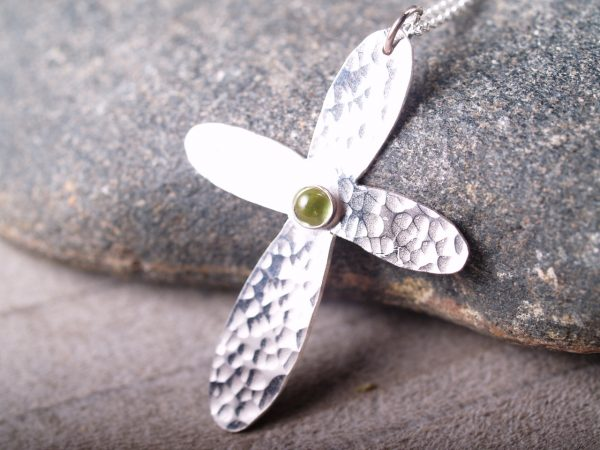 sterling hammered cross with rounded ends with a round peridot cabochon set in the middle shown on grey stone