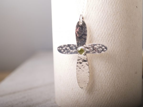 sterling hammered cross with rounded ends with a round peridot cabochon set in the middle shown hanging on white background
