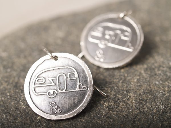 round sterling silver earrings with etched travel trailer design with French hooks closeup on granite