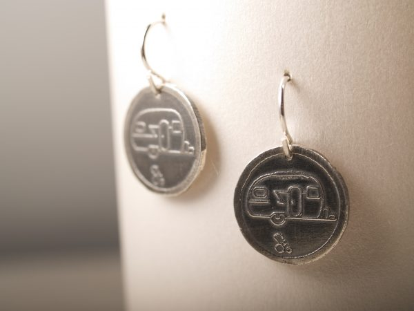 round sterling silver earrings with etched travel trailer design with French hooks hanging on white background