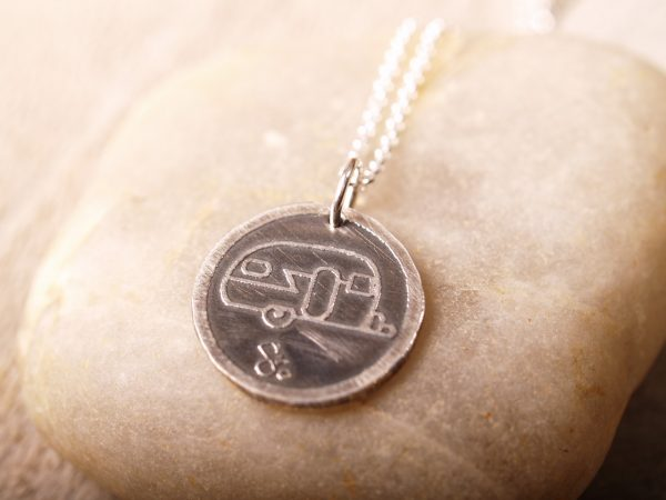 sterling round pendant with etched travel trailer design on silver chain midrange shot on stone