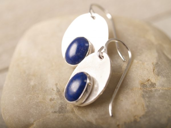 shiny sterling oval dangle earrings with smaller oval lapis cabochons set at the bottom of the oval close up shot on sandstone