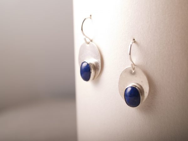 shiny sterling oval dangle earrings with smaller oval lapis cabochons set at the bottom of the oval mid range shot hanging on white background