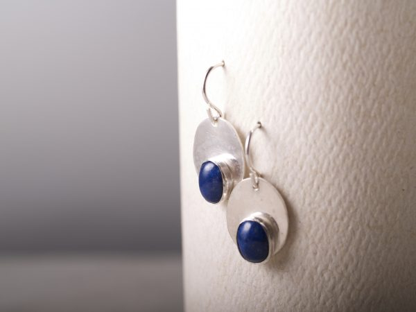 shiny sterling oval dangle earrings with smaller oval lapis cabochons set at the bottom of the oval midrange shot hanging on white background