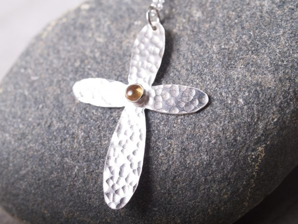 sterling hammered cross with rounded ends with a round citrine cabochon set in the middle shown on granite