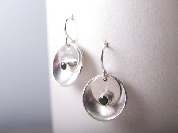 silver mirror and tab faceted emerald earrings hanging on white