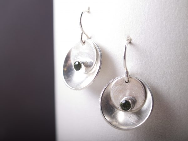 silver mirror and tab faceted emerald earrings hanging on white with brown