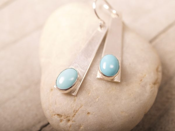 sterling silver trapezoid dangle earrings with turquoise oval cabochons shot on stone and wood background