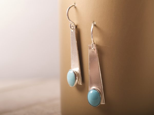 sterling silver trapezoid dangle earrings with turquoise oval cabochons shot hanging on gold