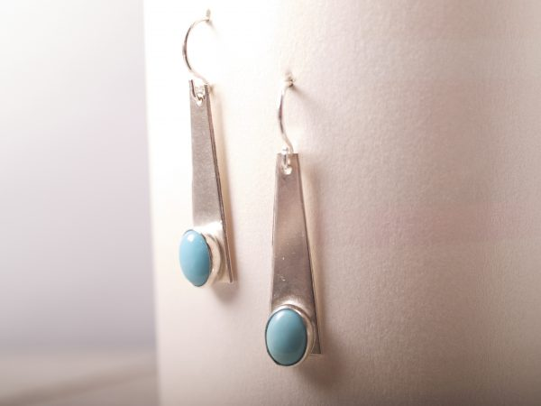 sterling silver trapezoid dangle earrings with turquoise oval cabochons shot hanging on white background
