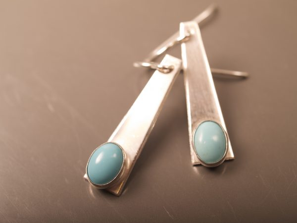 sterling silver trapezoid dangle earrings with turquoise oval cabochons shot on smoke background