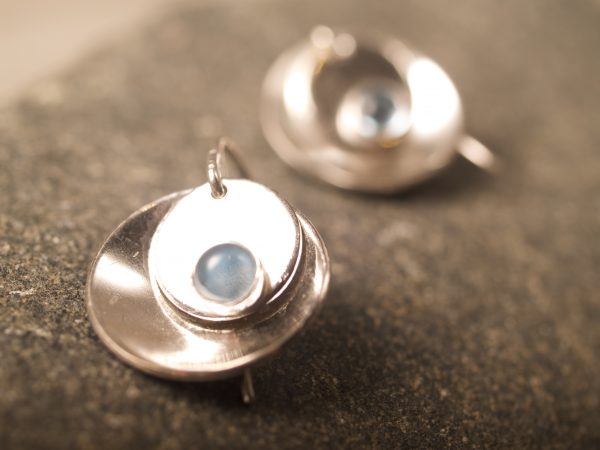 silver mirror and tab round blue topaz cabochon earrings - detail shot on granite