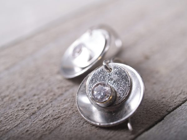 silver mirror and tab earrings with faceted CZ stones - laying on barn wood background