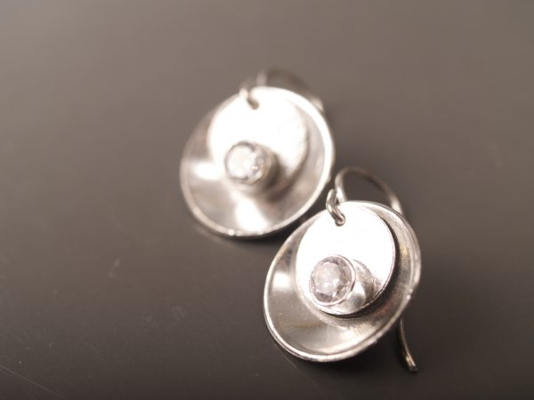silver mirror and tab earrings with faceted CZ stones - laying on slate background