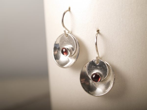 silver mirror and tab garnet cabochon earrings hanging on white