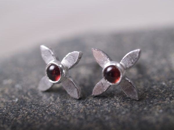 sterling flower cross stud earrings with round garnet cabochon centers - shot on blackstone