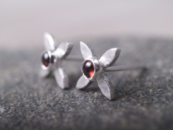 sterling flower cross stud earrings with round garnet cabochon centers - shot angled on blackstone