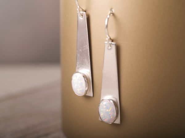 sterling silver trapezoid dangle earrings with opal oval cabochons shot hanging on gold background