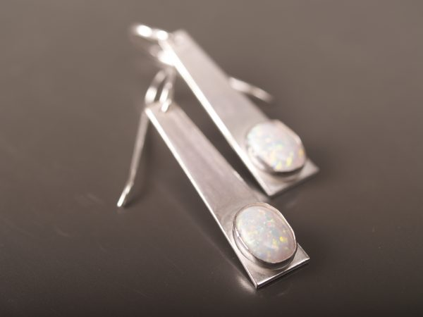 sterling silver trapezoid dangle earrings with opal oval cabochons shot on shiny slate