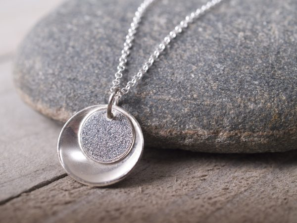 small round sterling pendant concave outside with lightly textured flat disk that sits inside the larger one toward the top - shown on dark granite