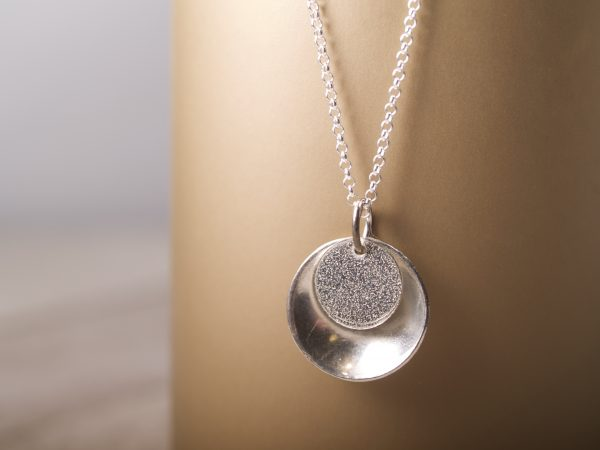small round sterling pendant concave outside with lightly textured flat disk that sits inside the larger one toward the top - shown hanging on gold background