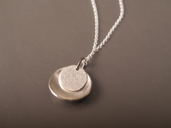 small round sterling pendant concave outside with lightly textured flat disk that sits inside the larger one toward the top - shown laying on slate background