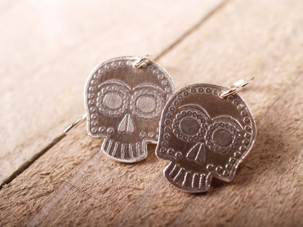 sterling sugar skull earrings on French hooks on a grey barnwood background