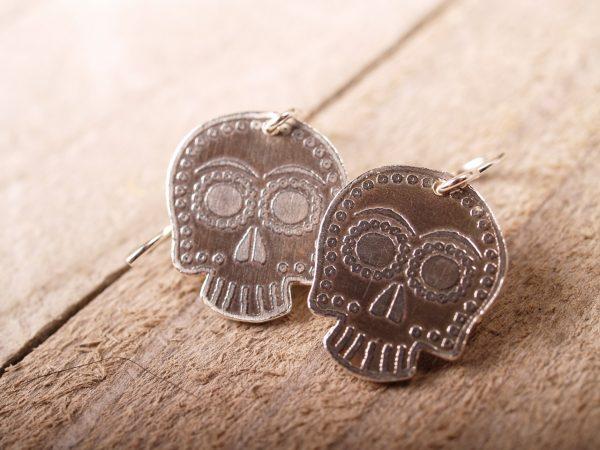 sterling sugar skull earrings on French hooks on a grey barnwood background