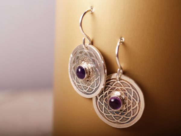 sterling disk etched earrings with mandala pattern and amethyst cabochon in the center. French hooks, hanging on bronze background