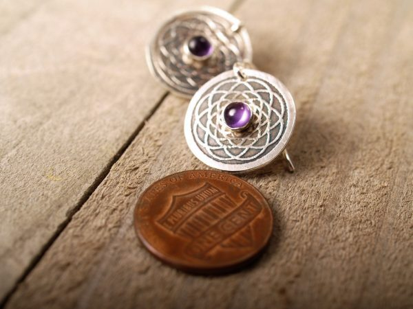 sterling disk etched earrings with mandala pattern and amethyst cabochon in the center. shown with penny for scale