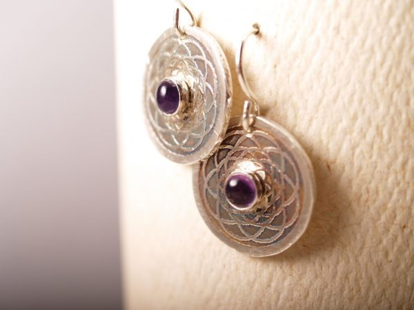 sterling disk etched earrings with mandala pattern and amethyst cabochon in the center. French hooks, hanging on white background