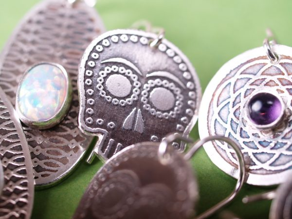 grouping of several new earring designs with sugar skull in middle