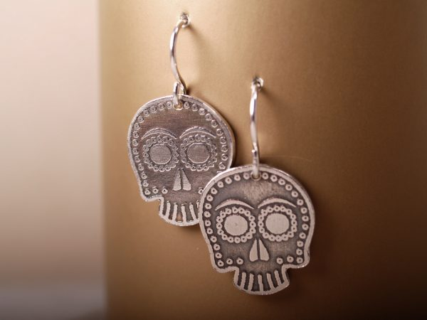 sterling sugar skull earrings on French hooks hanging on a bronze background