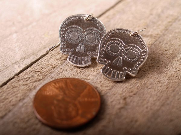 sterling sugar skull earrings on French hooks on a grey barnwood background with a penny for scale