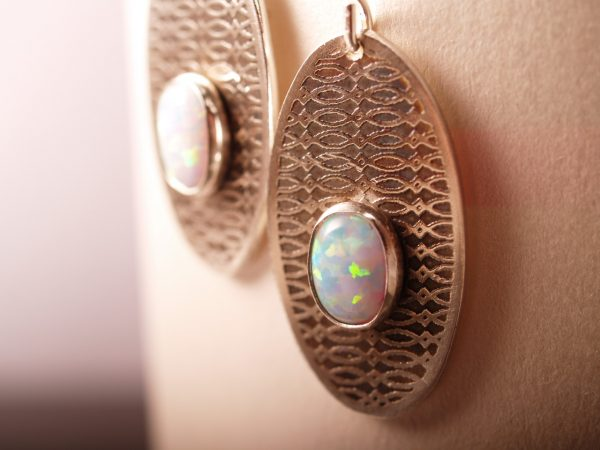 sterling dangle etched earrings with oval opal cabochons. French hooks hanging on white