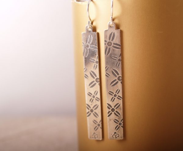 Rectangle dangle sterling silver earrings on French hooks with an etched pattern of large and small cross-shaped flowers shot hanging on gold background